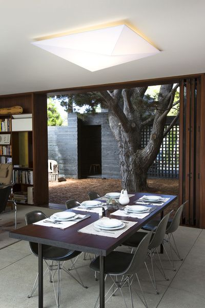 Michael Sylvester's Home, Venice, California. The dining area looking onto the Pine Needle Courtyard. The striking Ukiyo G Ceiling/Wall Combo light by AXO Light was sourced from Lumen...