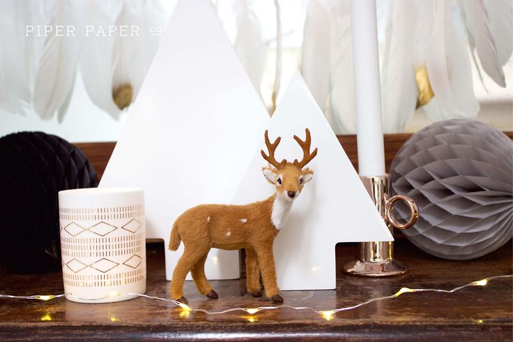 A very boho chic Christmas mantle. Nothing says boho glam like a gold dipped feather garland, copper candle holders, honeycomb balls and of course copper string christmas lights. Oh and a reindeer to top it off.