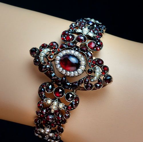 An Exquisite Victorian Era Renaissance Revival Antique Garnet Bracelet  of an elaborate openwork design, centered with an oval cabochon garnet (carbuncle) within seed pearl surrounding.   The bracelet is hand crafted in silver and completely covered with rose-cut glowing red Bohemian (pyrope) garnets highlighted with seed pearl scrolls and trefoils.   circa 1870