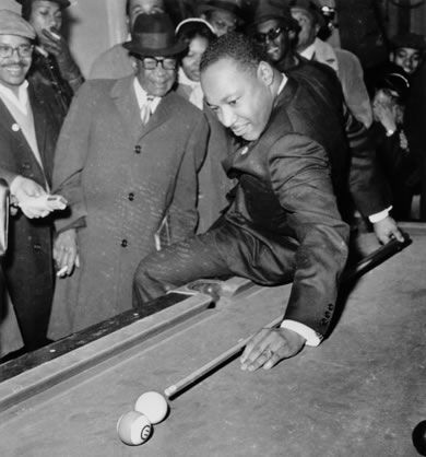 """""""King tries a difficult behind-the-back shot while using his """"best stick"""" in a pool match with Chicago civil rights leader Al Raby, while on an anti-slum campaign in 1966."""""""