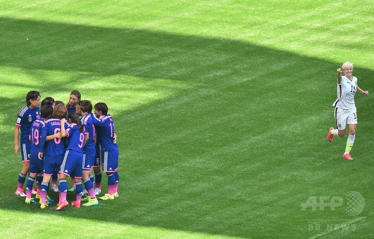 女子サッカーW杯カナダ大会・決勝、米国対日本。米国のミーガン・ラピノーが得点を喜ぶ中、円陣を組む日本の選手(2015年7月5日撮影)。(c)AFP/NICHOLAS KAMM ▼6Jul2015AFP|【写真】なでしこジャパン完敗、W杯連覇ならず http://www.afpbb.com/articles/-/3053699 #2015_FIFA_Womens_World_Cup #Final_United_States_vs_Japan