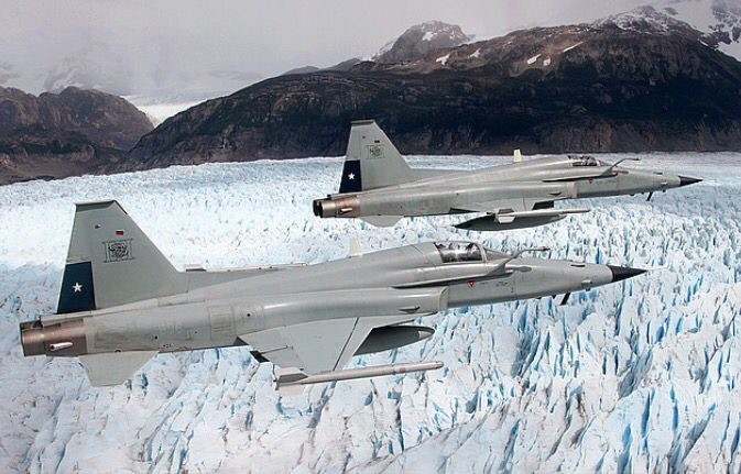 A pair of Chilean Air Force Northrop F-5E Tiger III fighters fly over a glacier.