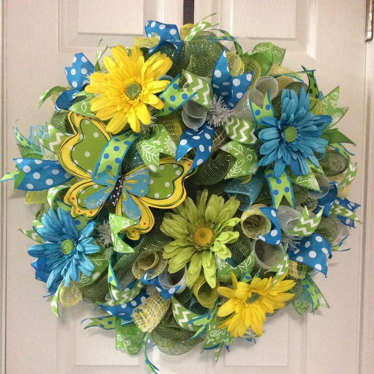 """""""Spring Butterfly Wreath""""($99) Spectrum of blues, greens and yellow all in one! This wreath is 28""""x28""""x8""""deep, on a white frame, moss green deco mesh, wood butterfly embellishment, yellow, green, turquoise blue gerber daisies, 2.5"""" turquoise polka dot ribbon, 2.5"""" lime green/white print ribbon, 1.5"""" lime green/white chevron ribbon, 1.5"""" lime/turquoise polka dot ribbon and white/blue/yellow deco curls. If interested, please message me. Thank you!"""