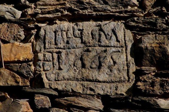 Detall d'una inscripció gravada sobre un bloc de pedra al poble de Bixissarri, parròquia de Sant Julià de Lòria, Principat d'Andorra. Es tr...