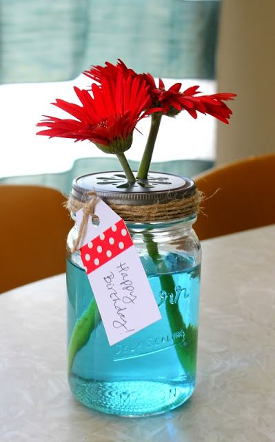 Mason Jar Vase. A drop of blue food coloring mixed in with the water is easy and pretty. Add a decorative lid, slide in a couple of daisies and wrap with twine. Such a simple gift idea.