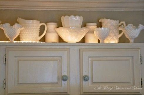 Rope light on the top of a kitchen cabinet.  Cheap solution to make the milk glass or china look amazing!