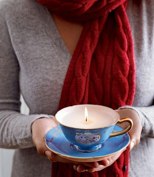Homemade candles presented in old teacups for a vintage touch.