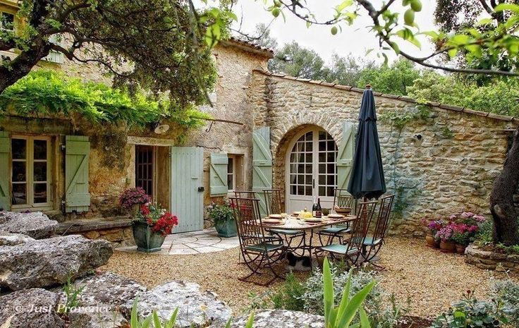 mediterraner Garten, Steinfassade, Holzmöbel, Pflanzen, Bäume