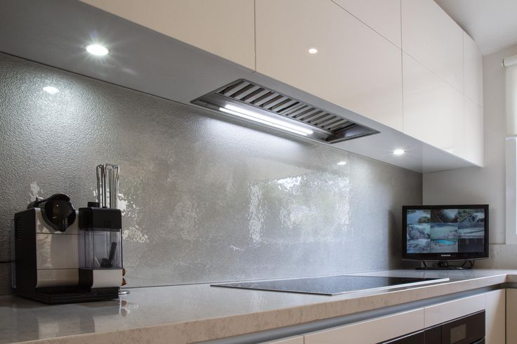 Glass splashback. Under mount rangehood. Induction cooktop. www.thekitchendesigncentre.com.au