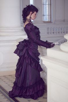 From the Steampunk Fashion Guide to Skirts & Dresses: Bustle Skirts - an example of a woman dressed in victorian costume wearing a purple bustle dress/skirt