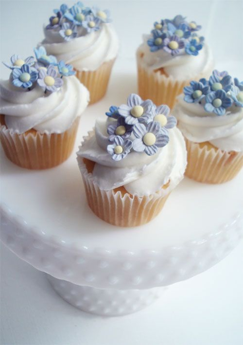 Forget-me-not cupcakes displayed on milk glass. Beautiful.