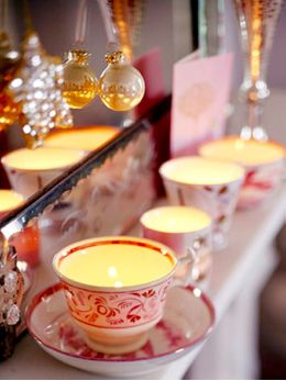 Take those mismatched porcelain teacups from the back of the china cabinet and use them for an illuminating mantel display. Choose tea lights that have plastic or metal holders to protect the insides of the cups from wax. A mirror placed behind the row of cups reflects the flickering light.
