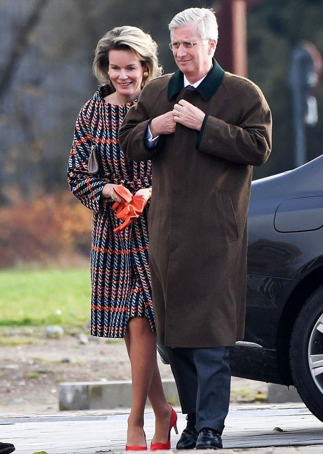Queen Mathilde of Belgium wrapped up against the chilly winter weather in a bold houndstooth coat which was streaked with blue, orange, white and black by Natan. She teamed with a pair of orange heels, matching leather gloves and a clutch bag. As she joined King Philippe of Belgium, looked smart in a white shirt, tie and practical green overcoat, as they visited the Den Diepen Boomgaard farm in Grimbergen.