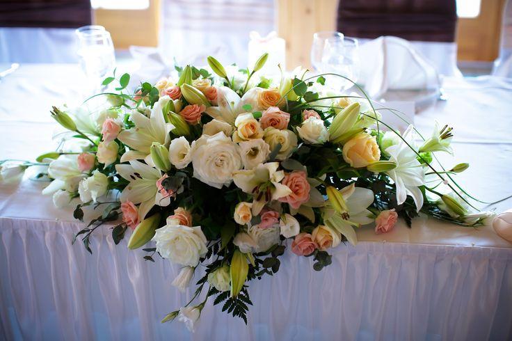 Mesés, pasztellszínű főasztaldísz esküvőre rózsából, liliomból.