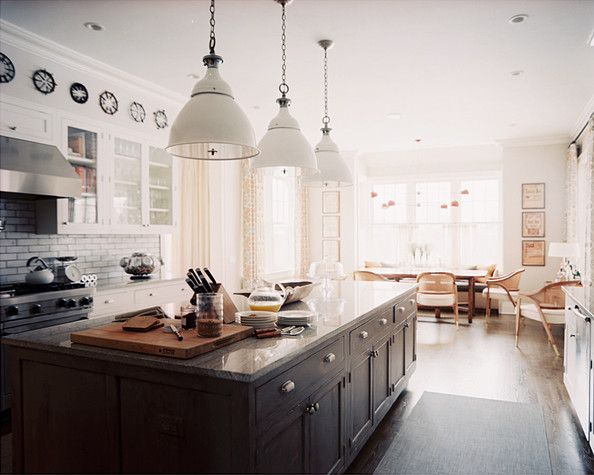 White enamel factory shade pendants by Ann Morris Antiques line the granite-topped kitchen island. The backsplash is sheathed in Grove Brickworks tiles by Waterworks.