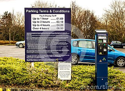 Pay and Display carpark pricing notice with terms and conditions next to an electronic ticket machine.