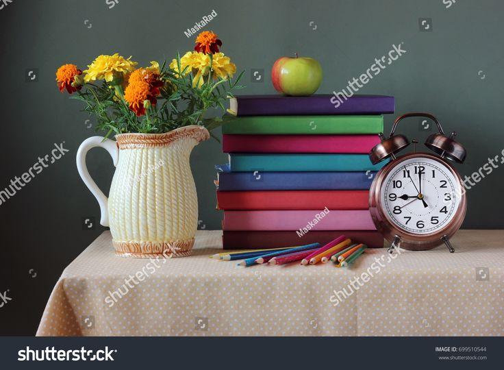 Стопка книг с яркими обложками, букет, часы, Яблоко, и цветные карандаши в стаканчике на столе. Обратно в школу. 1 сентября, День знаний. День учителя.