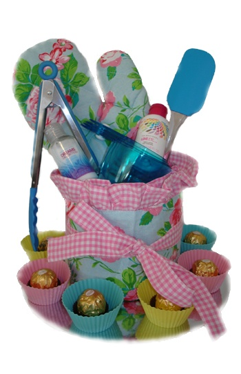 Flowers & Frills Cake    $70.00  3 Tea towels (inside to form cake)  1 Apron (outside of cake)  2 Mini body shop lotions  1 Tongs  1 Pot holder  1 Spatula  1 Set of measuring cups  6 Reusable cupcake holders  6 Fererro rochers
