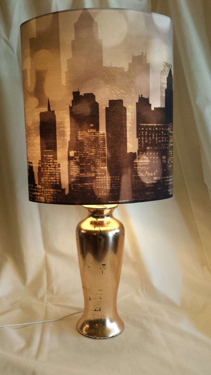 City Scape. I love this gold base and cityscape shade together. Both new and both very good quality, just waiting for the top floor of the Chrysler Building!
