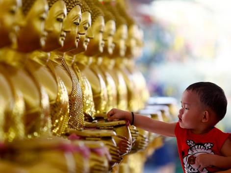 Petaling Jaya, Malaysia A child drops coins into golden Buddha statues as a symbol of blessings on Vesak Day at the Thai Buddhist Chetawan Temple in Petaling Jaya, near Kuala Lumpur, Malaysia, May 13, 2014.