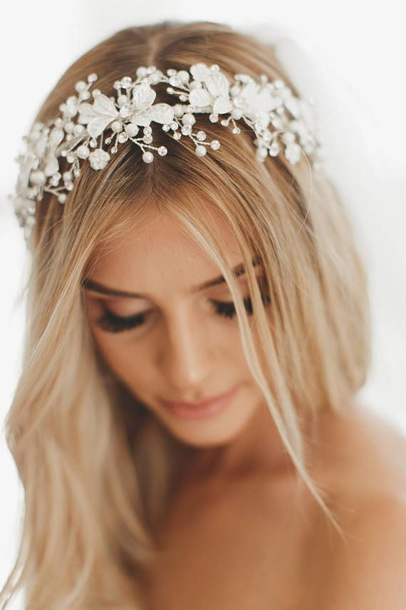 Our lovely bridal wreath is packed with Freshwater Pearls and glistening Swarovski crystals. This soft bohemian bridal crown is adorned with three ivory blossom flowers on each side. Available in both gold and silver wreath options. Exclusively at Veiled Beauty.  Freshwater Pearl Bridal Wreath, Style #1739  - Silver or Gold with Swarovski Crystals - Half crown. Loops on each end to tuck into hair and bobby pin (pins not included) - Limited supply available - No custom changes available in…