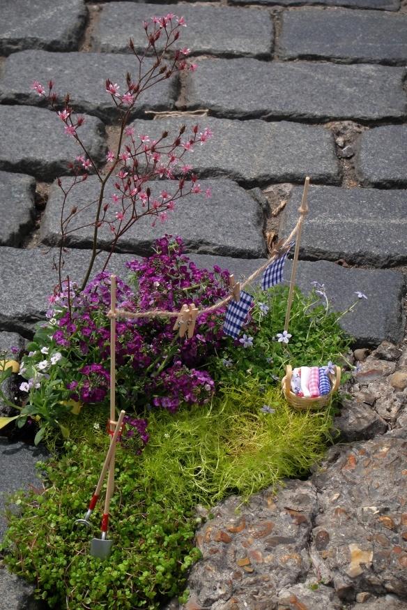 The pothole gardener.  Cute little clothes line and laundry basket. http://restreet.altervista.org/steve-wheen-ripara-le-buche-stradali-con-mini-giardini/