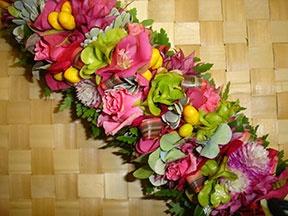 Pink haku lei with green aalii and yellow ohai alii.
