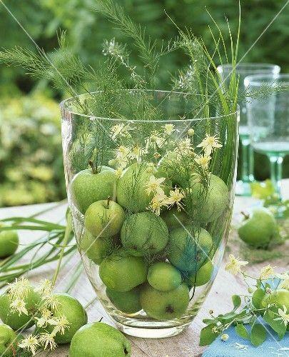 Grüne Äpfel, Zierspargel und Waldrebe in grosser Glasvase