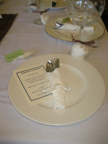 beach themed bridal bunch place setting. Silverware tied with ribbon and shell, menu card, name place card in shell and shell shaped soap favors.