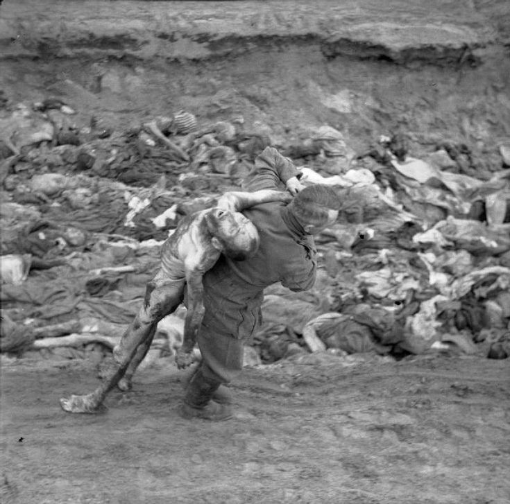 THE LIBERATION OF BERGEN-BELSEN CONCENTRATION CAMP, APRIL 1945. A German SS guard carries an emaciated corpse over his shoulder to one of the mass graves.
