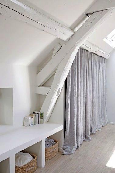 De grandes étagères se dissimulent derrière ce rideau : elles permettent de créer un espace de rangement ou un dressing sous les combles.