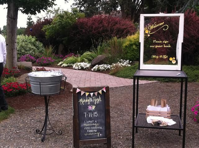 Potting table to sign guest book and a water bucket holder. What a great welcome for a wedding