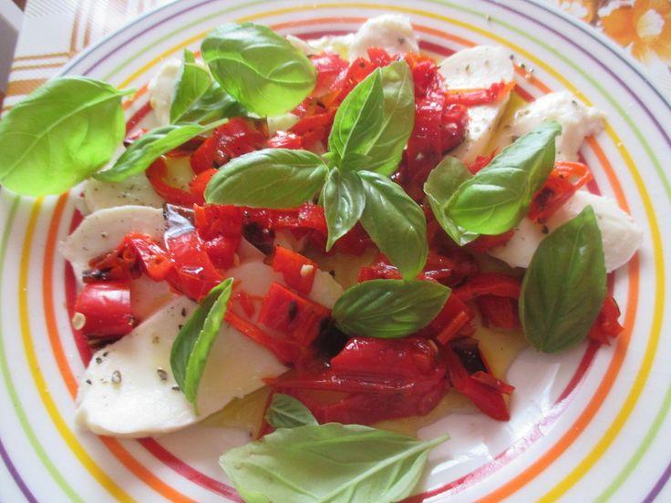 Mozzarellu nakrájejte na silnější plátky a rozložte na větší talíř.Chilli papričky na sucho pomalu opečte na grilu nebo na větší rozpálené pánvi....