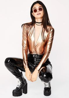 Gold Milla Metallic Bodysuit cuz yer just a baddie at heart, bb. This sexy metallic gold bodysuit has a deep crossover v-neckline, long sleeves, and a cheeky fit.