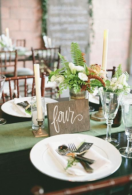 A rustic, wooden table number with custom calligraphy | Brides.com