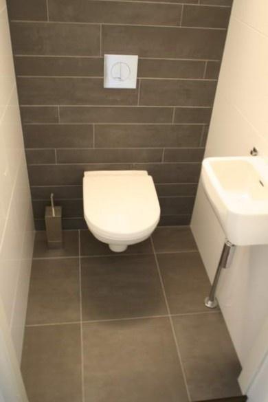 Tegels:  achterwand donker, zijwanden licht. Wit toilet