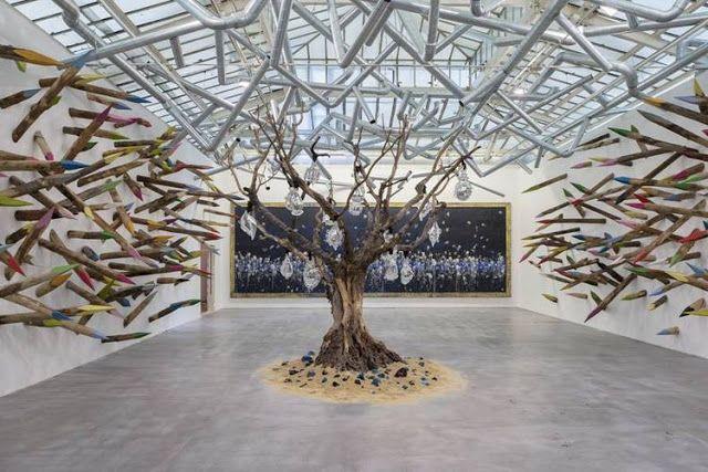 """Vue de l'Exposition, """"Gri-gri"""", 2015, Paris, VNH Gallery. Aux murs des crayons pointus et colorés (Douces épines, 2015), au plafond des réseaux de tuyaux (Lianes métalliques, 2015), au centre de la salle, entouré de sable et de cristal coloré, un olivier/baobab où sont accrochés des masques de cristal (Arbre de Vie, 2015), et au fond de la salle, un tableau noir aux projections de silicone blanc (Fresque deArtPlastoc: 382-L'OEUVRE DE PASCALE MARTHINE TAYOU AU TRAVERS DES QUESTIONS DU…"""