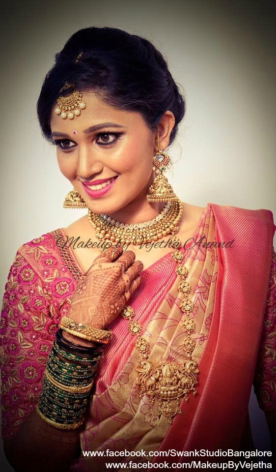 Our bride Padmavati (Rithika) looks gorgeous for her reception in a pink silk saree and bridal antique jewellery. Makeup and hairstyle by Vejetha for Swank Studio. PHOTO CREDIT: Manish Ananda. Pink lips. Jhumkas/Jhumkis. Bangles. Statement necklace. Silk sari. Bridal Saree Blouse Design. Indian Bridal Makeup. Indian Bride. Gold Jewellery. Statement Blouse. Tamil bride. Telugu bride. Kannada bride. Hindu bride. Malayalee bride. Find us at https://www.facebook.com/SwankStudioBangalore