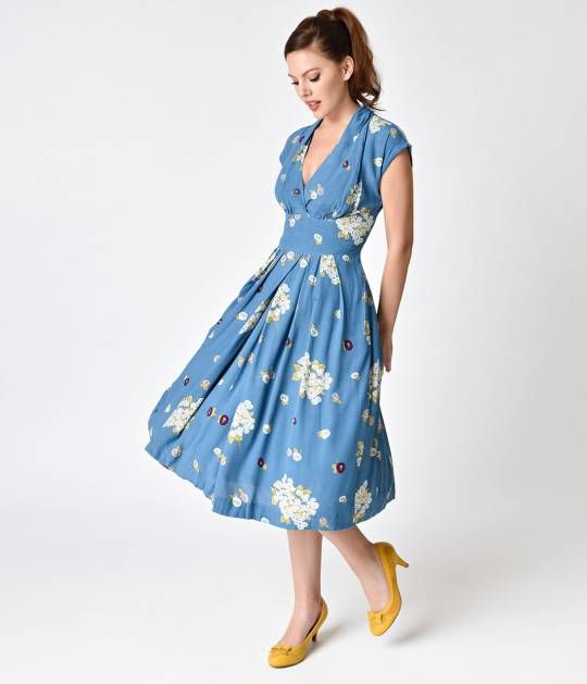 Emily and Fin brings us Flora, the box pleated, and lightweight lined blooming swing dress! This 1930s inspired blue frock features a draped v-neck with cap sleeves, and its dappled with a unique floral print. The semi-full pleated skirt features a high,