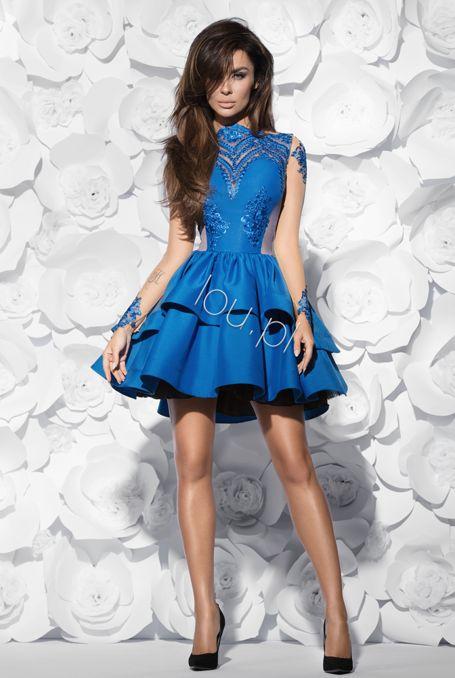 Chabrowa sukienka o wyjątkowym kroju dla kobiet lubiących się wyróżniać. Góra uszyta z koronki z delikatnymi cekinkami podszyta cielistą tkaniną, dół rozkloszowany z trzema usztywnionymi falbanami. Z tyłu zapinana na kryty zamek.