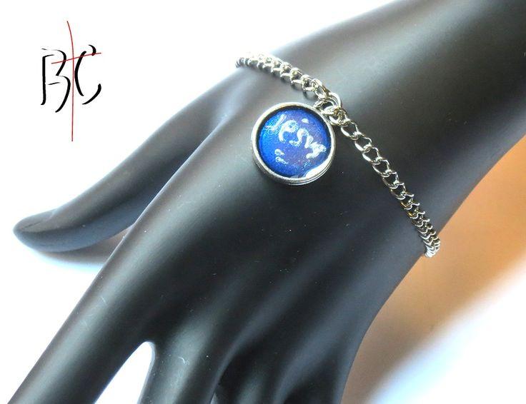Bracelet breloque Jésus couleur bleu  Bracelet ajustable chaîne en acier inoxydable Breloque en métal alliage Dimension 14 mm Couleur argent antique avec design Couleur bleu vitrail écrit Jésus à la main avec peinture couleur argent. Le tout recouvert de résine