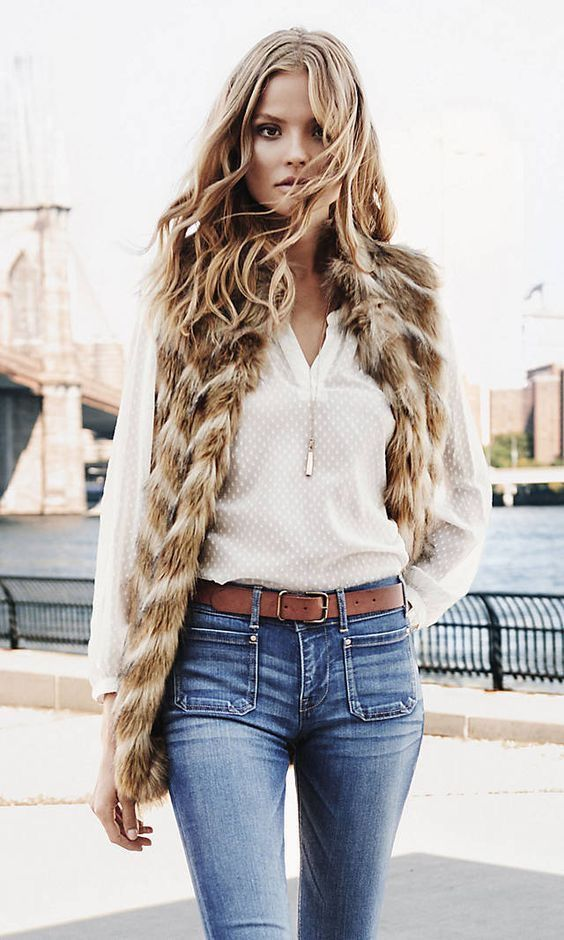 Faux fur vest over white blouse and blue jeans.