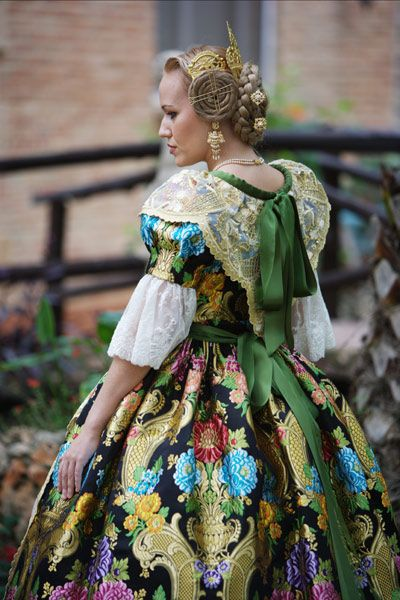 Fallera, regional dress of Valencia, Spain. Gold combs and pins secure the elaborate hair style.