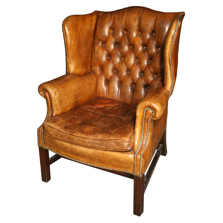 wingback chairs in the library and family room one of them in worn leather