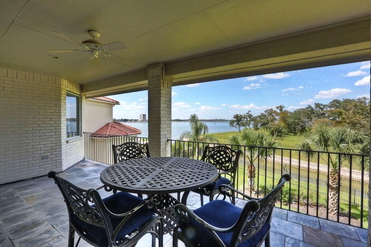 Upper covered terrace has an outstanding view of Clear Lake and canal. With slate flooring, iron railing, & ceiling fan, the terrace is a stylish viewing location.