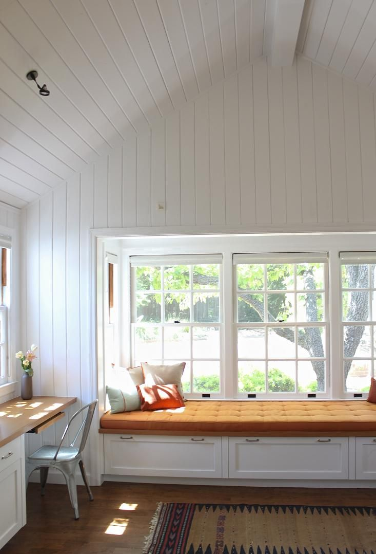 V-groove white beadboard in Mark Reilly guest house, Remodelista  like the cover on window seat