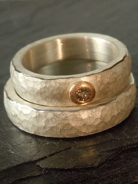 Trauringe, schlicht und edel, aus Silber mit gehämmerter Oberfläche. Den Damenring ziert ein aparter champagnerfarbener Brillant , eingefaßt in ei...