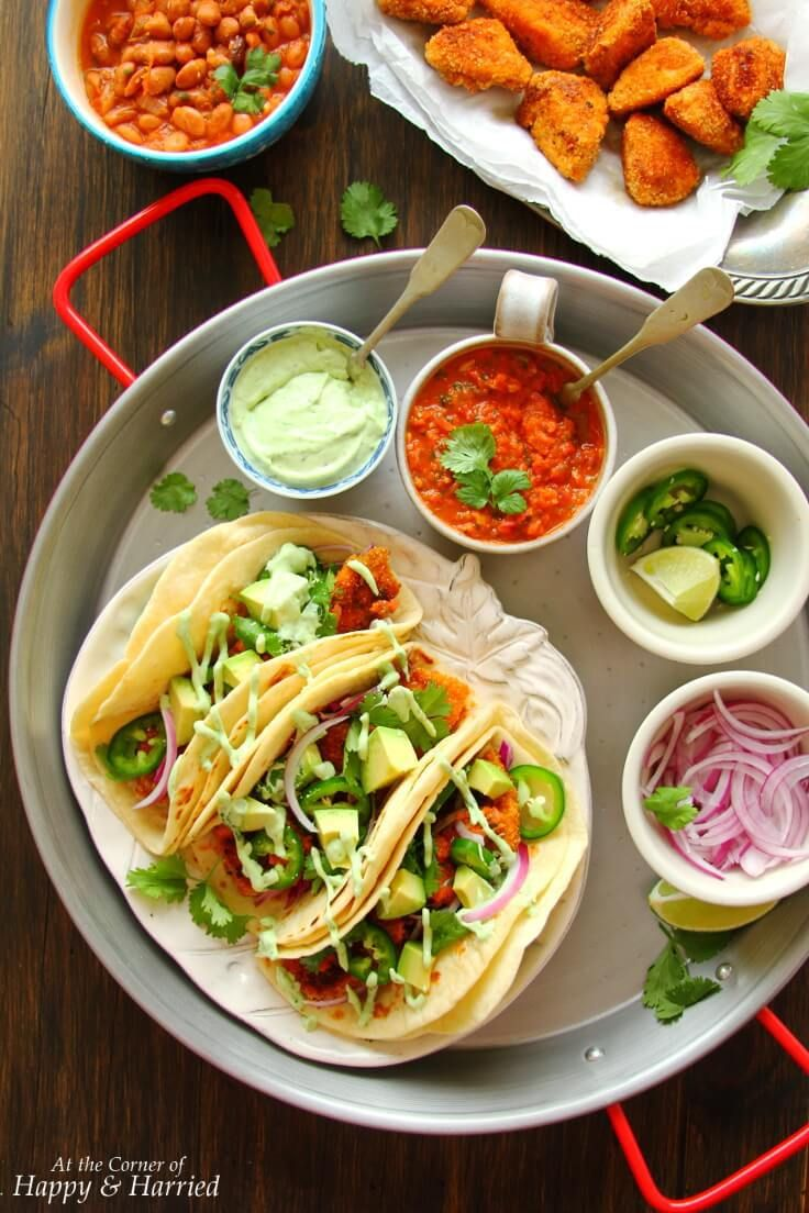 FRIED SALMON TACOS WITH SALSA RACHERA & AVOCADO CREMA - HAPPY&HARRIED. Crispy pan-fried #salmon bites are encased in soft tortillas and served with homemade #salsa ranchera and a cool #avocado crema for a delicious Mexican fiesta! #happyandharried #taco #recipe