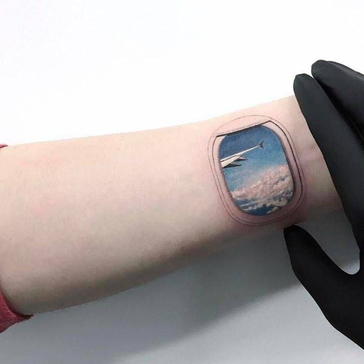 Airplane window tattoo on the left inner wrist.
