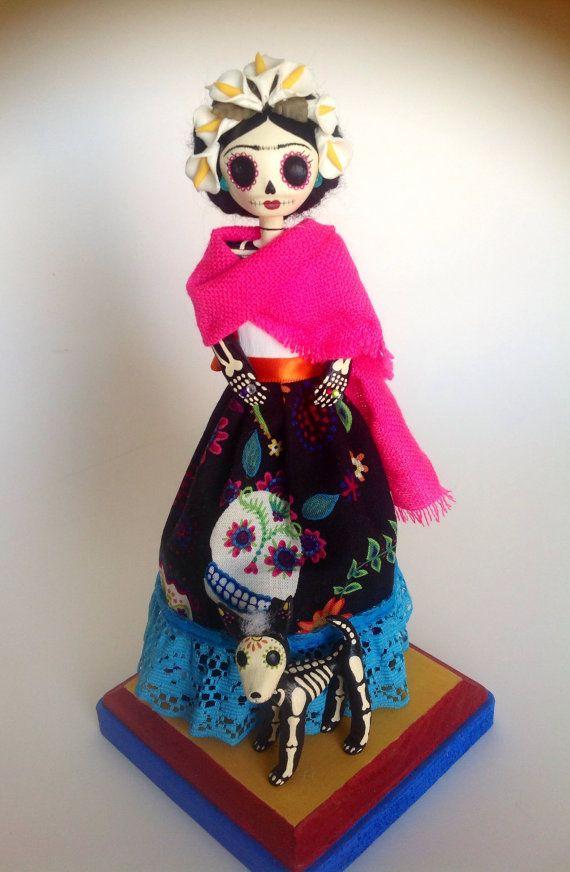 Frida no podía tener hijos debido al autobús accidente sucedido a ella en el año de 1925. Como sustitutos para los niños ella recogió muchas muñecas y mascotas como monos, perros, pájaros y hasta un ciervo. En este recuerdo, Frida es uno de sus perros mexicanos Itzcuintli. Esta clase de perro es muy rara y costosa. Ella es tranquila como pasar la tarde en el jardín de La Casa Azul    Pequeña Frida kahlo catrina mache de papel hecho a mano, mide 20 cms altura (23 cms aprox. incluye base de…
